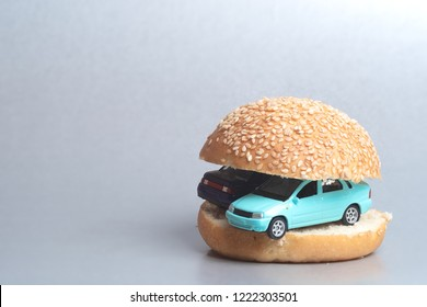 on a gray background between the hamburger buns which toy cars, not real burgers