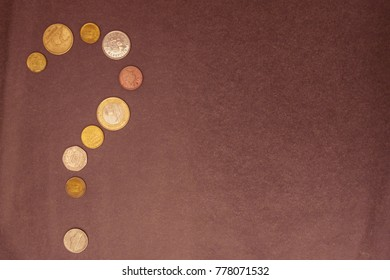 On a gray background, a question mark made up of small coins. Family budget, money issue, lack of funds. View from above.