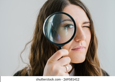 on a gray background young girl looking through a magnifying glass