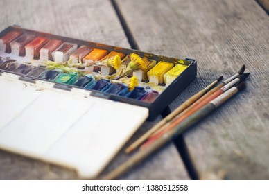 On a gray wooden table are vintage watercolor paint in a box with cuvettes, along with which are yellow flowers coltsfoot and a few brushes for drawing.