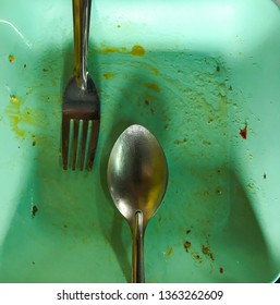 on the green dish has a spoon and fork but empty food after lunch