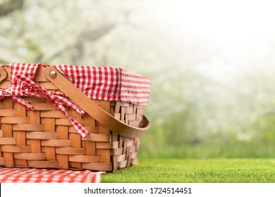On green grass, a picnic basket against the backdrop of the landscape. A backdrop for relaxing and spending the weekend. Picnic and relaxation