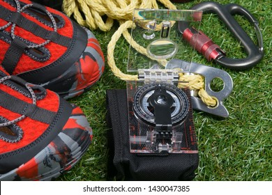 on the green lawn, close-up, set for the traveler, comfortable shoes, compass, rope and carabiners