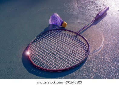 On the green surface of the table, covered in dew in the morning light of the sun, are a racket and a shuttlecock to play badminton, instagram.