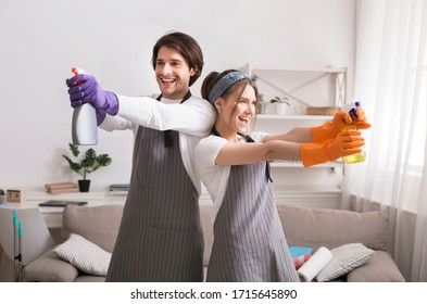 On guard of cleanliness. Funny young couple fooling while cleaning apartment, aiming with detergent sprayers, standing back to back in living room