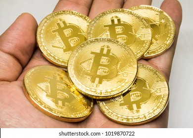 ?hold on hand gold metal coin cryptocurrency bitcoin on white background
