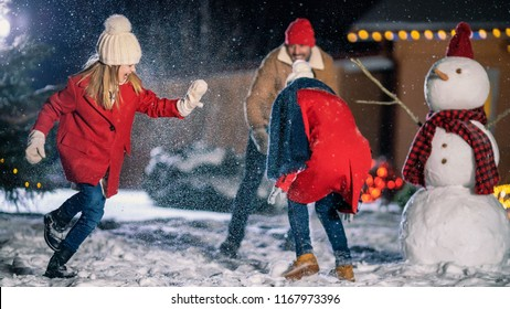 On the Happy Winter Evening Young Father, Mother and Cute Little Daughter Play in Snowballs, Running around the Snowman. In the Background Their Idyllic House Decorated with Garlands.