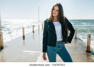 On her a black leather jacket, blue jeans and a white t-shirt. The girl gently looks in a distance and sea wind pleasantly irons her dark hair as if playing with them.
