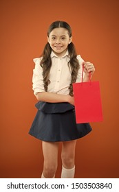 On her weekly shopping. Adorable shopper or shopping addict on orange background. Little girl smiling with shopping bag. Happy small child holding red paperbag after shopping.