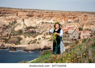 on a high seashore cheerfully walks a round charming woman in a wreath of flowers and a rural folk puritan dress