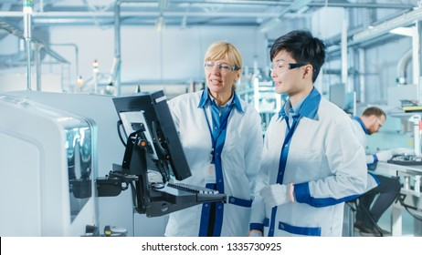 On High-Tech Factory Asian Engineer Talks with Female Supervisor, Use Computer for Programming Pick and Place Electronic Machinery for Printed Circuit Board Surface Mount Assembly Line. Production
