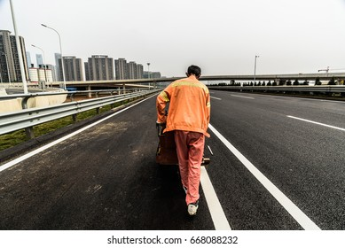 On the highway transport workers to the road cross the white solid lines