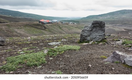 On the hills with sparse vegetation there are houses of the tourist base. Cloudy. In the foreground is a large picturesque boulder. Kamchatka