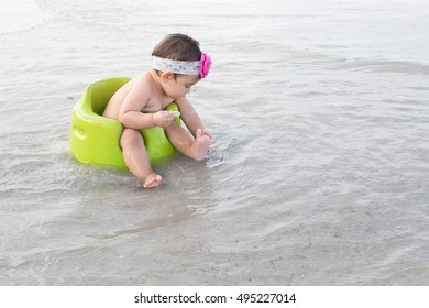 On holiday,pretty child sit in green chair to play sea water on beach.