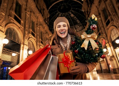 On a huge Christmas sales in Italian fashion capital. Portrait of cheerful elegant woman with Christmas tree and shopping bags in Galleria Vittorio Emanuele II in Milan, Italy