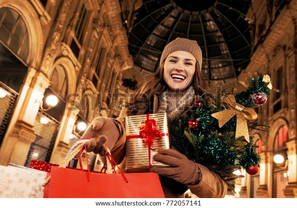 On a huge Christmas sales in Italian fashion capital. Portrait of smiling modern traveller woman with Christmas tree in Galleria Vittorio Emanuele II in Milan, Italy showing shopping bags