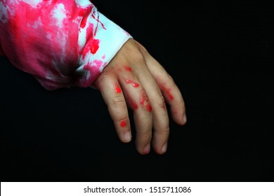 On the human hand, natural blood flows down against a dark background, hand of boy