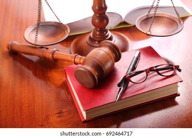 On the judge's table,gavel, scales, books, glasses and pen