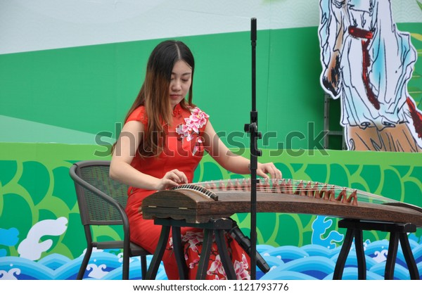 On June 16, 2018, a woman wearing a qipao in the romain district of xi 'an world expo garden attracts visitors to watch the performance of violins, guzheng, erhu and pipa. Dragon Boat Festival.