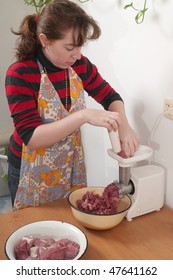 On kitchen the electrical meat grinder works. The woman prepares a mincemeat.