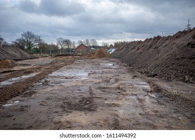 on a large construction site, excavators are used to remove topsoil so that a foundation for a large factory building can be built
