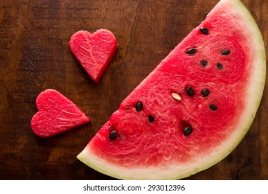 On the left side 2 hearts from the pulp watermelon and watermelon slice on the right on the wooden table. Slice of watermelon and 2 hearts. Top view. Close-up. Daylight. Horizontal shot.