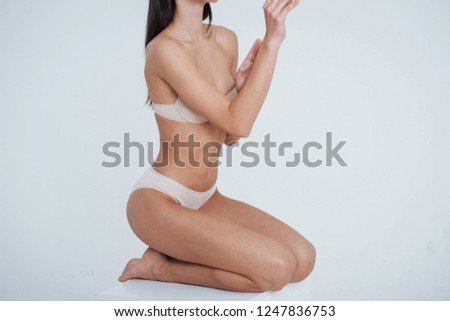 45be2834577 On the legs. Girl with perfect slim toned young body sitting in the studio  with