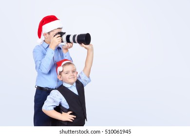 On the light background brothers are photographing in Santa Claus caps