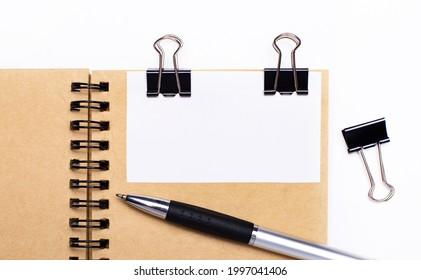 On a light background, a brown notebook with a pen, black clips and a white card with a place to insert text or illustrations. Template.