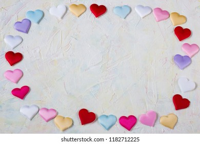on a light background multicolored hearts from satin - background for Valentine's day, wedding, engagement