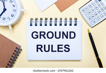 On a light background, a white alarm clock, a calculator, a pen and a notebook with the text GROUND RULES. Flat lay