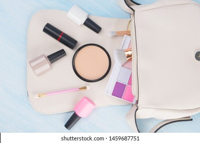 on a light background, from a white cosmetic bag, scattered items for manicure and makeup, colored eyeshadow, brushes , face powder, nail Polish and red lipstic