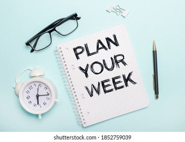 On a light blue background lie black glasses and a pen, a white alarm clock, white paper clips and a notebook with the words PLAN YOUR WEEK. Business concept