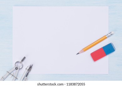 on a light, blue background a sheet of white paper and a set of metal objects for graphics, a pencil and an eraser