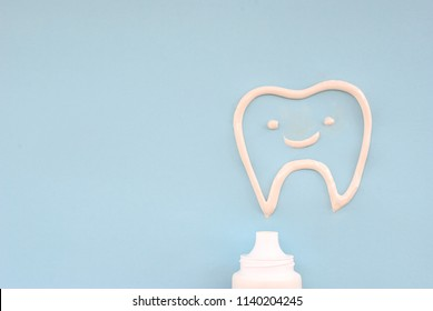On a light blue background a toothpaste in the form of a smiling tooth is squeezed out of the tube, a conceptual backdrop