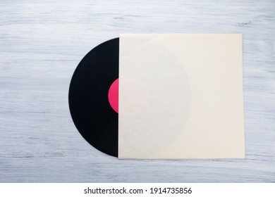 on a light gray background is a vinyl record in a paper envelope