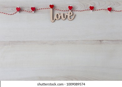 on a light wooden background a rope, clothespins with hearts and the word love