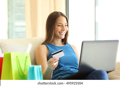 On line buyer shopping on line with credit card and a laptop sitting on a sofa with shopping bags beside at home