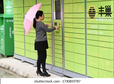 On May 14, 2020, in a residential quarter in Huai'an City, Jiangsu Province, China, residents are picking up express mail, and couriers are putting express mail in Fengchao boxes.