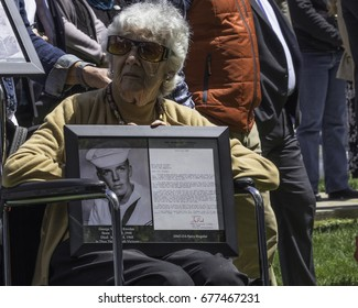 On May 4, 2017, the University of New Hampshire hosted the Traveling Memorial Wall for the community of Portsmouth (New Hampshire). This woman displays picture of her lost son during the Vietnam war.