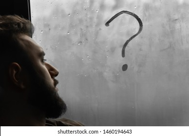 on the misted window glass an exclamation mark is drawn, on the side of the face of a pensive young man with a beard. concept of obscurity
