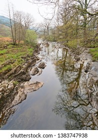 On a misty day in April the crystal clear water of the River Mawddach flows slowly through the countryside on Gwynedd, Wales.