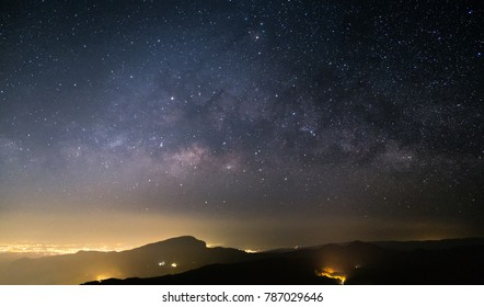 On the mountain at night there is a Milky Way and a full sky. And the mountains are light from the city.