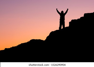 on the mountain, the silhouette of a man with his hands up against the dark sky. overcame a steep climb and rejoices in his victory man on the background of the sunset sky on the mountain
