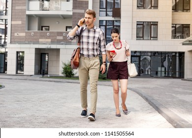 On the move. Confident young man having a phone conversation while going to work with his wife