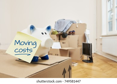On a moving box there is a piggy bank on which a yellow piece of paper sticks. The note is in English language. On the note is moving coats. In the background is a stack of packed moving boxes