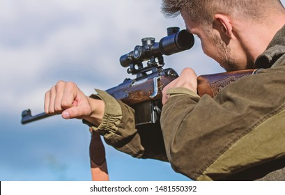 On my target. Bearded hunter spend leisure hunting. Hunting optics equipment for professionals. Brutal masculine hobby. Man aiming target nature background. Aiming skills. Hunter hold rifle aiming.