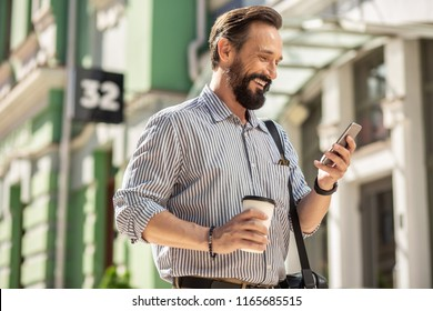 On my way to work. Waist up of cheerful bearded man using his smartphone and drinking coffee