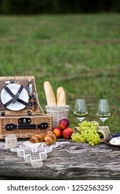 on the nature on a wooden table: picnic basket, bottle of wine, glasses of wine, baguette, croissants, grapes, peaches, Camembert cheese (vertical frame)