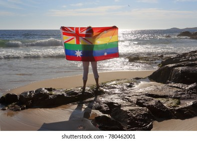 On November 15 Australia voted yes to Marriage Equality.  A woman holding an Australian flag in rainbow colours by the ocean